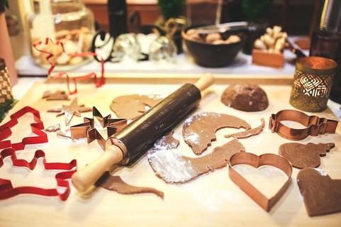 作業台の上にある型抜きされたクッキー生地とクリスマスの抜き型