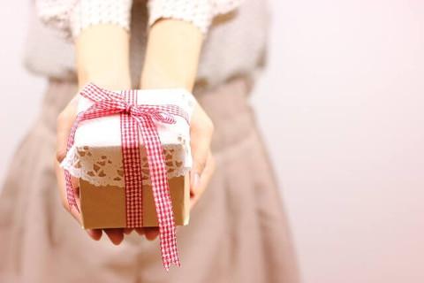 手作りラッピングのプレゼント箱を差し出す女性の手元