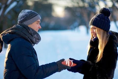 雪景色の中でプレゼントを手渡す女性と受け取る男性