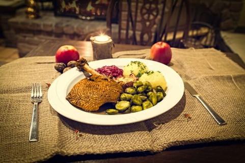 テーブルの上のローストされた鴨肉やマッシュポテトの乗ったディナーとリンゴ