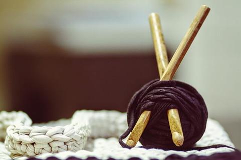 太いかぎ針が刺さった黒い糸玉と手編みの白いマット