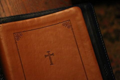 クロスが刻印された革のブックカバー
