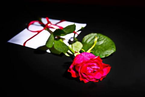 白い封筒とそれに結ばれた赤いリボンと赤い一輪のバラ