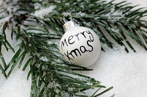 雪の上のもみの木の枝とメリークリスマスと描かれた白いオーナメント