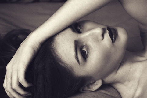 すぐ隣で寝ている距離で横たわり目線を向ける女性