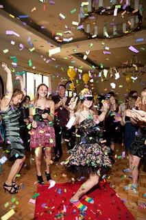 ドレスに身を包み紙ふぶきを浴びて踊る女性と日常を忘れて盛り上がるパーティー会場