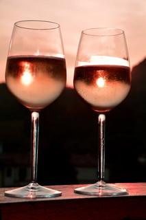デート気分を盛り上げるたっぷりとワインが注がれたグラスとグラスに映るサンセット