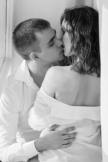 自宅で人目を気にせずラブな時間を過ごす白いシャツ姿のカップル