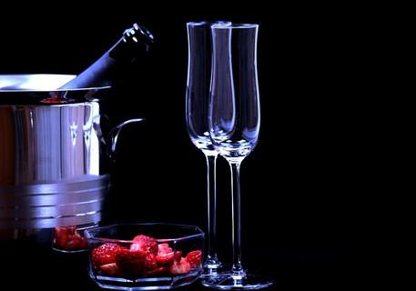 2人の気分を盛り上げてくれるワインクーラーで冷やされたシャンパンとグラスとお皿に入ったイチゴ