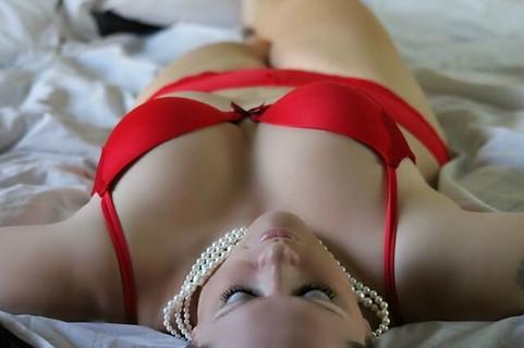 大晦日に勝負をかける赤い下着とパールのネックレスを身に付けベッドに横たわる女性