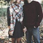 落ち葉の上に立ち手を握り合いひたいをくっつけるカップル