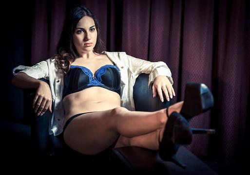 下着姿にシャツを羽織ソファに座る女性