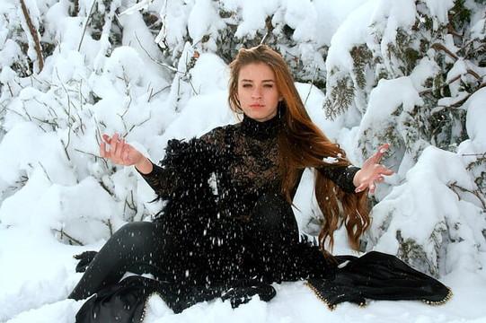 黒いドレスを着て雪の中に座り雪をまく女性