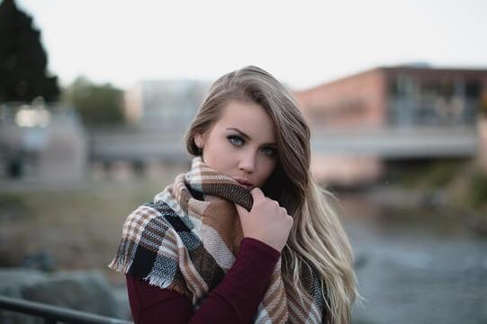 ボルドーのセーターにチェックのストールを巻いたブロンドヘアの女性