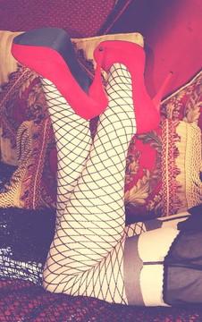 アミタイツとガーター柄がプリントされているストッキングをはく女性の足