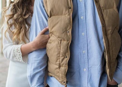 青いシャツにダウンジャケットを羽織った男性と手を絡める白い服の女性