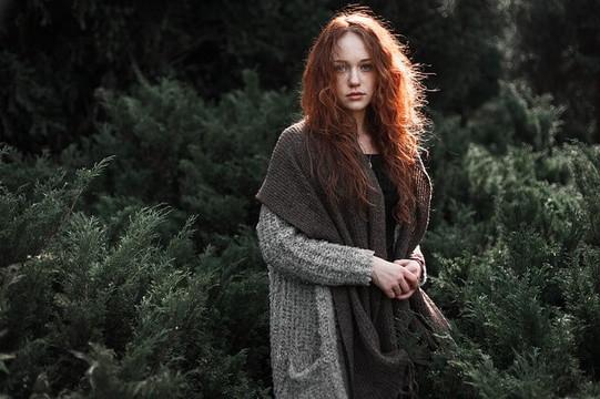 グレーのニットにベージュのストールを羽織った赤毛の女性