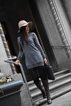 グレーのニットワンピを着てブーツをはき、階段を降りる女性