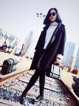 サングラスをかけ白いニットを着て黒いチェスターコートを羽織った女性