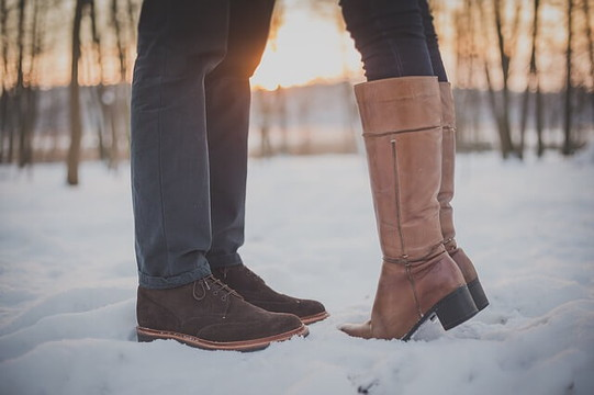 雪の上に立ってキスをする恋人の足元