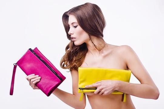 ピンクとイエローのクラッチバッグを持つ女性
