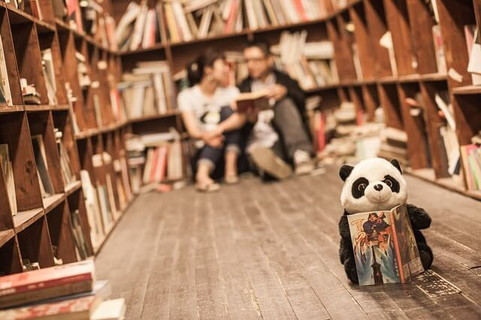 本棚に囲まれた部屋で床に座るカップルと本を持ったパンダのぬいぐるみ
