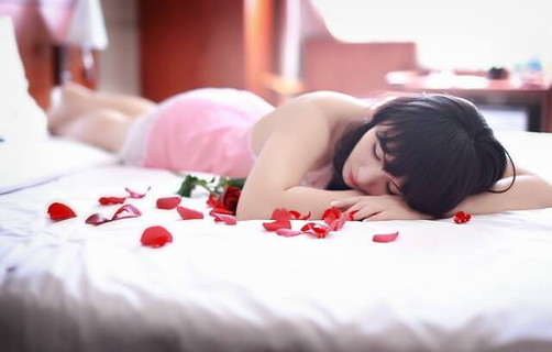 ピンク色のベビードールを着て白いベッドに横たわる女性と赤いバラのはなびら