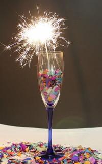 シャンパングラスに入ったカラフルな紙ふぶきと燃える花火
