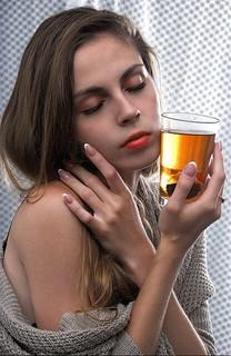 グラスを持ち目を閉じて肩をはだける女性