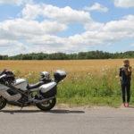 道端にバイクを止めて新しい出会いに期待しながら青空にみどりが広がる景色を眺める女性