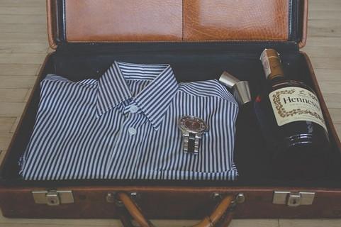 新しい恋愛を見つける旅の準備、トランクに詰め込まれたストライプのワイシャツとウイスキーボトルとショットグラス2つ