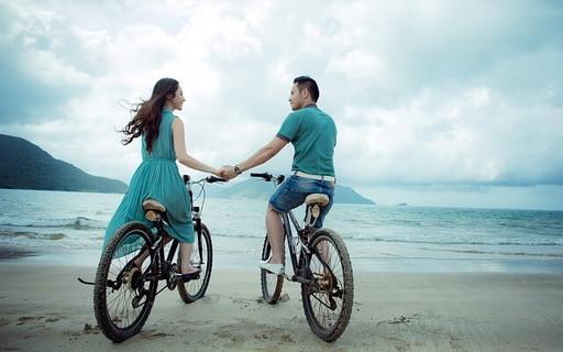 海を目の前に砂浜でマウンテンバイクに乗る旅先で運命的な出会いをした青い服の2人