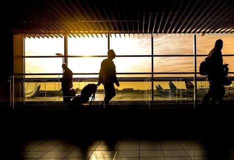 非日常の空気を味わいながら朝日が昇る中空港の通路をトランクを引いて歩く男性のシルエット
