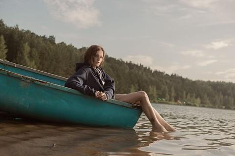 飾らない姿で青いボートに座り湖に足をつける女性
