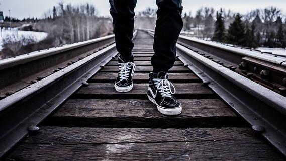 黒いスニーカーに黒いパンツ姿で線路の真ん中をずんずん歩く男性の足元