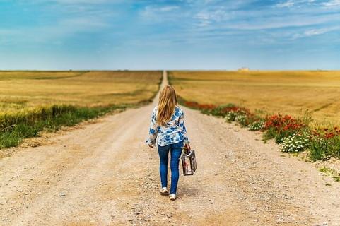 この道の先にどんな出会いがあるのかワクワクしながらトランクを持ち一本道を歩く女性