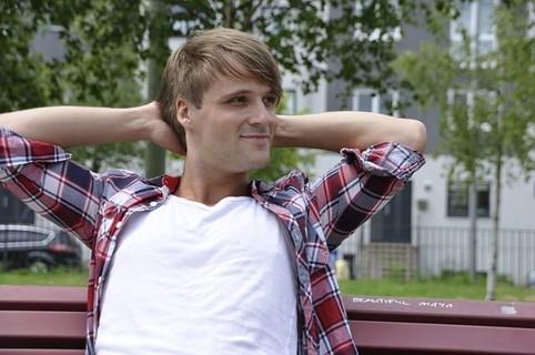 ベンチに腰を下ろし爽やかな笑顔で頭の後ろで腕を組む、一見良い人そうに見える男性
