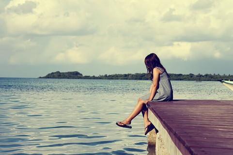 恋人と別れてひとりになろうかな…そんなことを考えつつうつむいて桟橋に座る女性