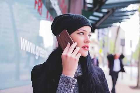 冷静に的確に、携帯電話で恋人に自分の意見を伝えるグレーのニットに黒いニットキャップを被った女性