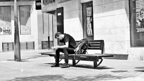 「どうせオレなんて」とベンチに腰かけ横にリュックを置きうつむく男性