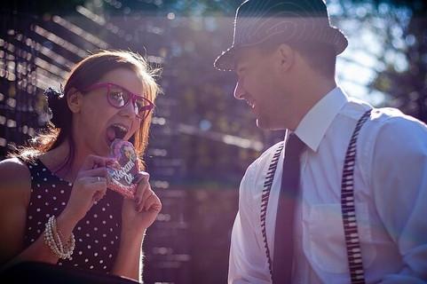 ハート型のアイシングクッキーを食べようとする女性とそれを笑顔で見守る男性