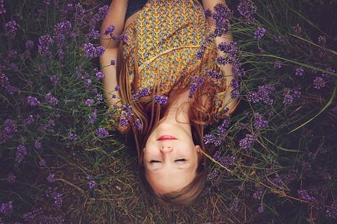 目を閉じてリラックスしラベンダー畑に寝転がる女の子