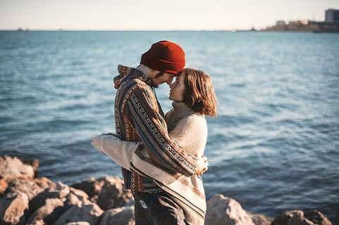 海を背景に岩の上で抱き合い額をくっつけ合うスキンシップを大切にしているカップル