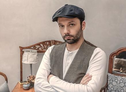 腕を組みバレンタインは必要ないのではないかと目で訴えかける帽子にベスト姿の男性