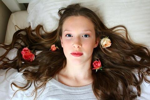 今年の自分チョコは何にしようかしらと考えながらベッドに仰向けになる女性とバラの花