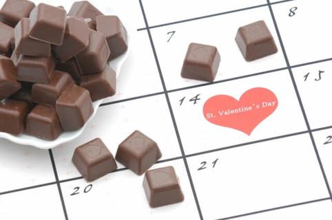 バレンタインデーに印がついたカレンダーとたくさんのチョコレート