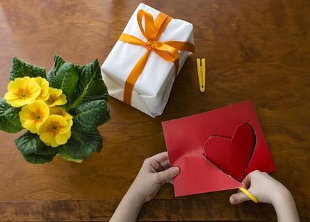 バレンタインチョコを包装し、さらに赤いハート型の飾りをつけようと奮闘する女の子の手元