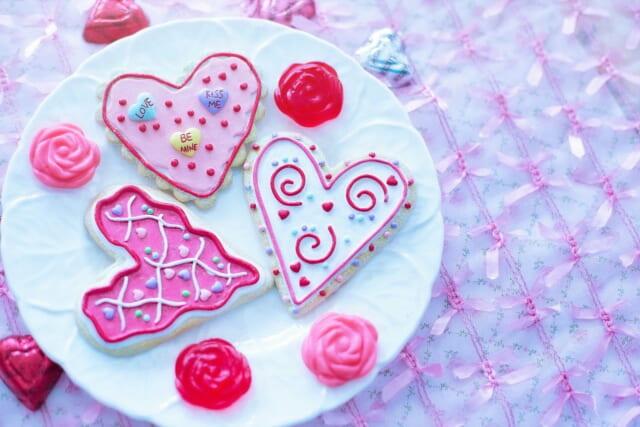 お皿の上に乗ったカラフルなバレンタインのデコレーションがほどこされた手作りアイシングクッキー