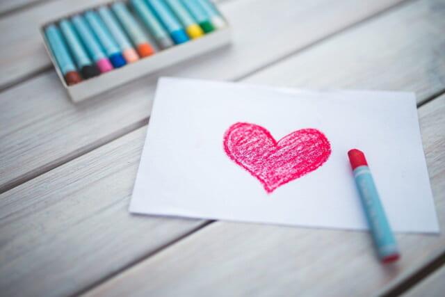 白い画用紙に赤いクレヨンでハートが書かれたシンプルな手紙
