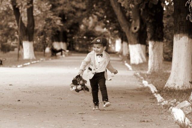 正装をしてフラワーバレンタイン用の花束を持って歩く小さな男の子